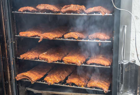 smoke rising around a slow cooked beef brisket on a smoker barbecue grilling concept