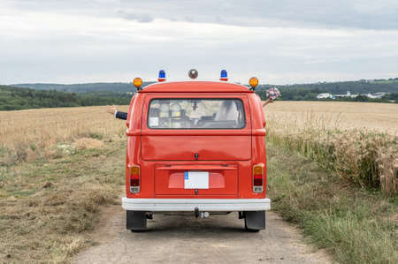 Ochtendung Germany 25.05.2019 Wedding Couple in Oldtimer VW T1 fire engine red firefigther car classic car drivin on the Road Editorial