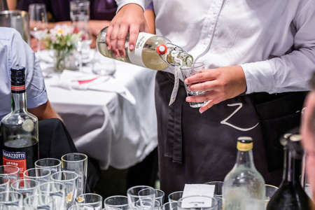 06.07.2019 Koblenz Germany hand with bottle of hazelnut alcohol liquor poured into a shot glass during a party wedding Editorial