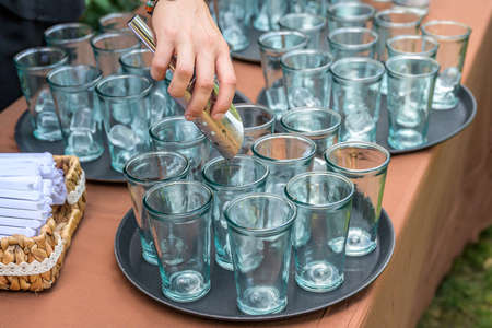 Bartender with spoon adding ice cubes to glasses during a wedding party