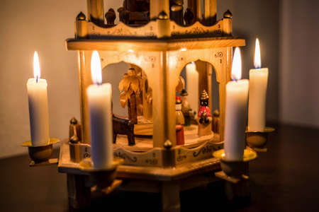 Traditional Christmas decoration Candles burning on a wooden carousel with nativity scene and wood sculptural characters Banco de Imagens
