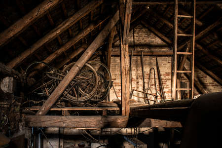 A rusty old vintage bikes in a barn with old farm machinery