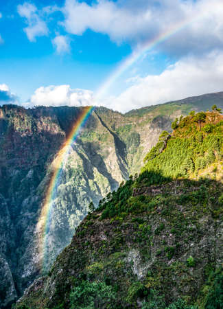 The beautiful Levada mountains lit up by a rainbow on the south side of Madeira, Portugal