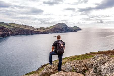 Man hiking rocky cliffs clear near water of Atlantic Ocean bay Ponta de Sao Lourenco, the island of Madeira, Portugal