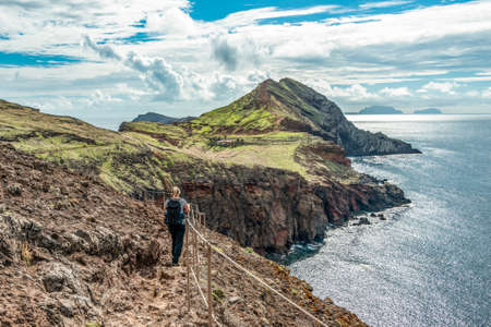 Girl hiking rocky cliffs clear near water of Atlantic Ocean bay Ponta de Sao Lourenco, the island of Madeira, Portugal Stock Photo