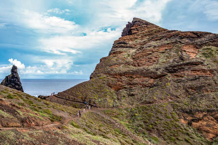 View of man hiking on rocky cliff clear water of Atlantic Ocean at Ponta de Sao Lourenco, the island of Madeira Portugal Stock Photo