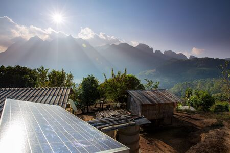 environmental issues: Mountains behind Solar panels Stock Photo