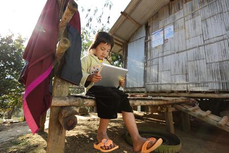 niños pobres: Chiang Mai Tailandia de diciembre de 28 de 2012: Niña que usa la tableta