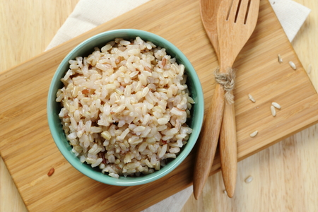 bowl with rice: Brown Rice on Wooden Plate