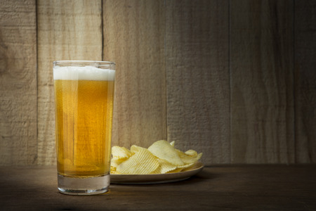 root beer: Beer Glass and Potato Chips on a Wooden Background