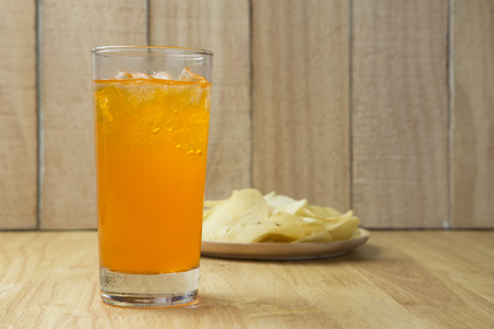 sodas: Refreshing Orange Soda with Ice and Potato Chips on a wooden background