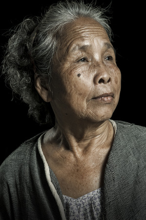 Portrait of asian senior woman. Over black background. Фото со стока