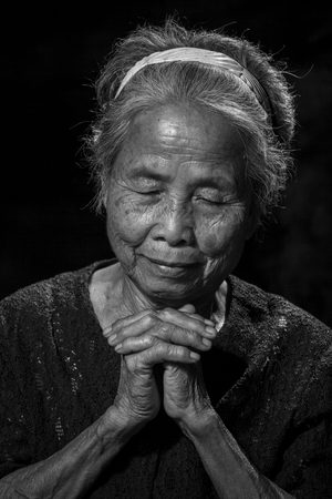 vecchiaia: Ritratto di una donna di alto livello che prega nero e colore Bianco Archivio Fotografico