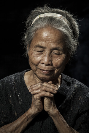 underdeveloped: Portrait of a senior woman praying Stock Photo