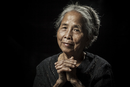 Old woman praying on black background