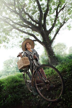 underdeveloped: Happy Asian elderly seniors couple biking in the park