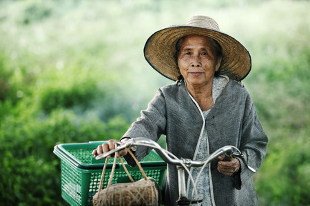 thailand: Old women couple with their bikes outdoors Stock Photo