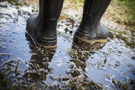 水たまりに長靴ラバーブーツを汚れや泥 写真素材