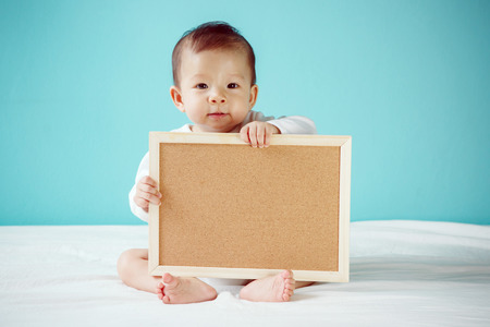 Infant child holding empty board studio shot