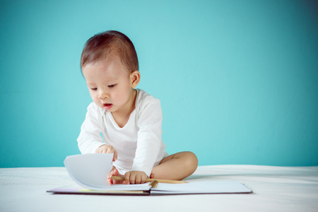 Asian baby writing in a book
