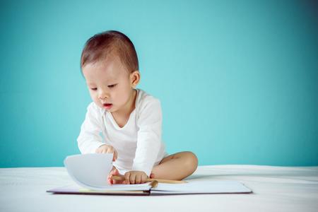 Aziatische baby in een boek schrijven
