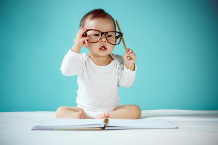 bebes: Bebé asiático lindo que miente en el estómago en la cama foto de estudio