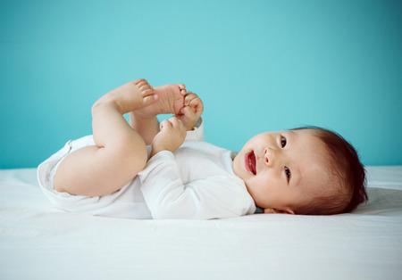 아기: 귀여운 7개월 아기의 초상화는 침대 새로운 가족과 사랑 개념에 누워.