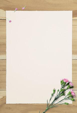 portapapeles: el Libro Blanco vacío y clavel rosado en mesa de madera