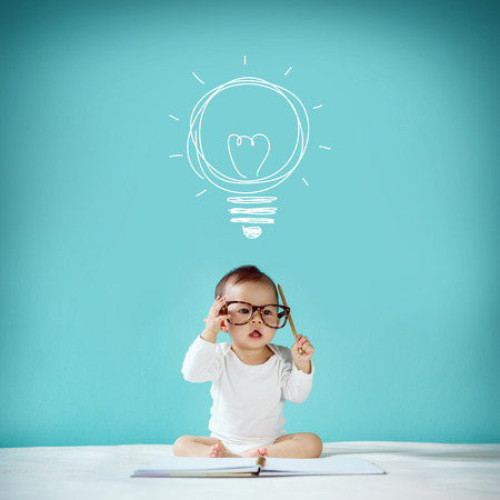 Concept idea of happy little baby with bulb at blackboard new family and love concept studio shot