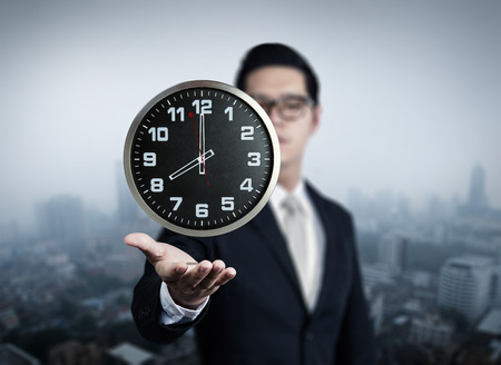 Businessman hand holding clock, new business in the city collection, studio shot