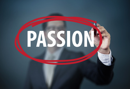 "Businessman hand writing ""PASSION"" with red marker on transparent board, new business concept, studio shot"