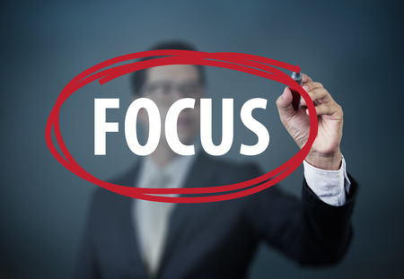 "Businessman hand writing ""FOCUS"" with red marker on transparent board, new business concept, studio shot"