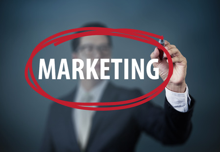 board marker: Businessman hand writing Marketing with red marker on transparent board, new business concept, studio  shot Stock Photo