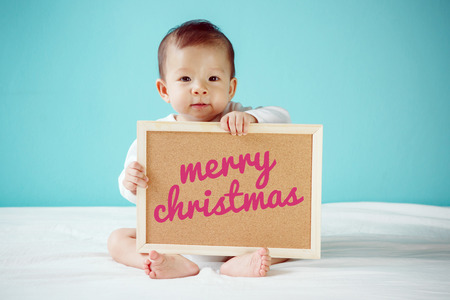 Baby writing Merry Christmas on the board, new family concept, studio shot