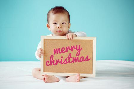 """bebes niñas: Bebé escribir """"Feliz Navidad"""" en el tablero, nuevo concepto de familia, foto de estudio"""