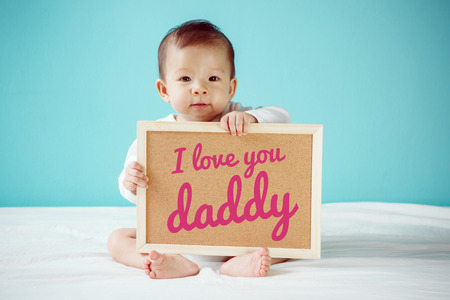 baby love: Baby writing I Love you Daddy on the board, new family concept, studio shot