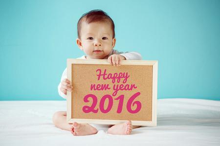 """Baby van het schrijven van """"Gelukkig Nieuwjaar 2016"""" op het bord, nieuwe familie concept, studio-opname"""
