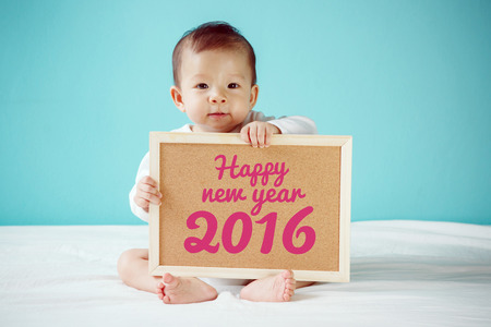 Baby writing Happy New Year 2016 on the board, new family concept, studio shot