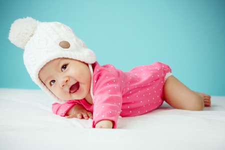 Little baby in knit winter clothing closing face with knitted beanie Stock Photo - 42742739