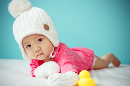 beanie: Baby wearing white knitted beanie in front of blue background Stock Photo