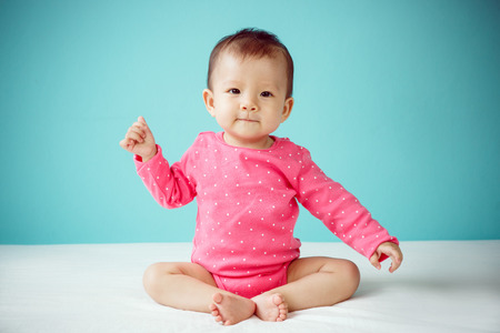 bebe sentado: Beb� asi�tico vistiendo ropa de color rosa Foto de archivo
