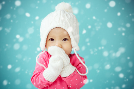 Baby with white poodle hat and knitted mittens with snow falling