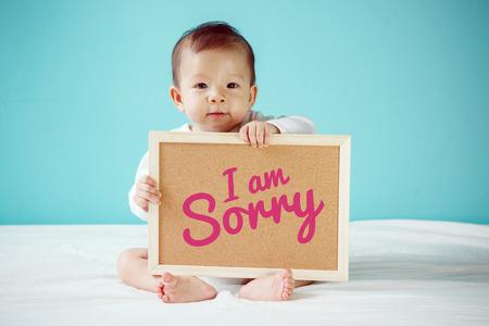 """Baby van het schrijven van """"Het spijt me"""" op het bord, nieuwe familie concept, studio-opname"""