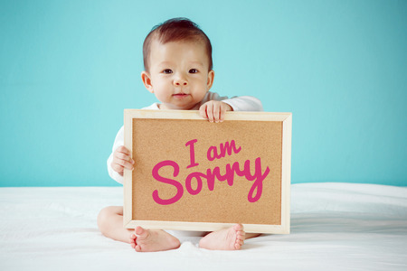 i am sorry: Baby writing I am Sorry on the board, new family concept, studio shot
