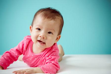 bebe sentado: Bebé asiático lindo que miente en el estómago en la cama, tiro del estudio