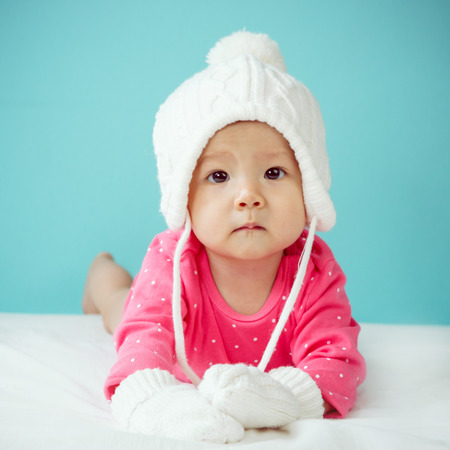 asian baby girl: Baby with white poodle hat and knitted mittens