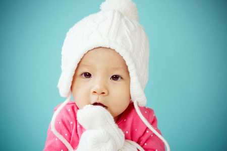 beanie: Little baby in knit winter clothing closing face with knitted beanie