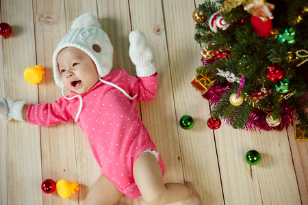 pink christmas: Infant child with white poodle hat and knitted mittens and Decorating Christmas tree on green background