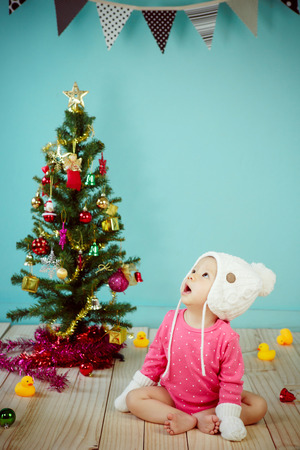 pink christmas: Baby wearing white knitted beanie in front of blue background and Decorating Christmas tree on green background Stock Photo