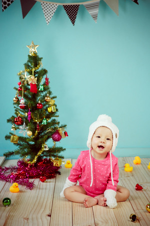 christmas gold: Little baby in knit winter clothing with knitted beanie and Decorating Christmas tree on green background